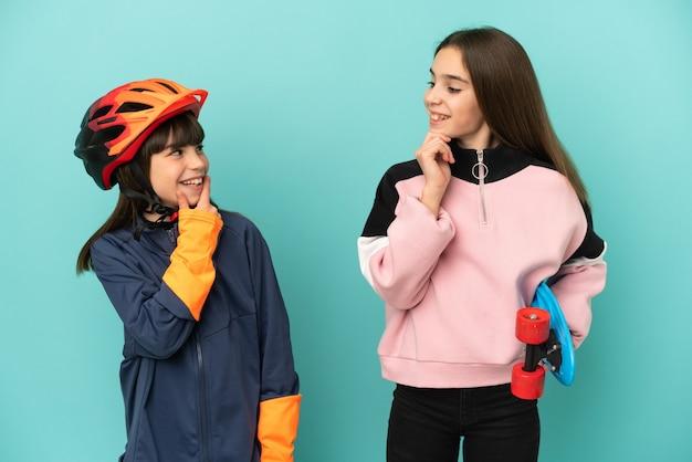 Kleine zusjes beoefenen fietsen en skater geïsoleerd op blauwe achtergrond kijken naar elkaar