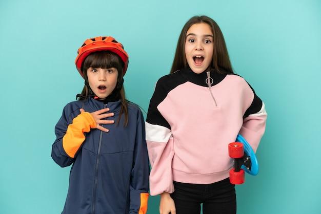 Kleine zusjes beoefenen fietsen en skater geïsoleerd op blauwe achtergrond met verrassing en geschokte gezichtsuitdrukking