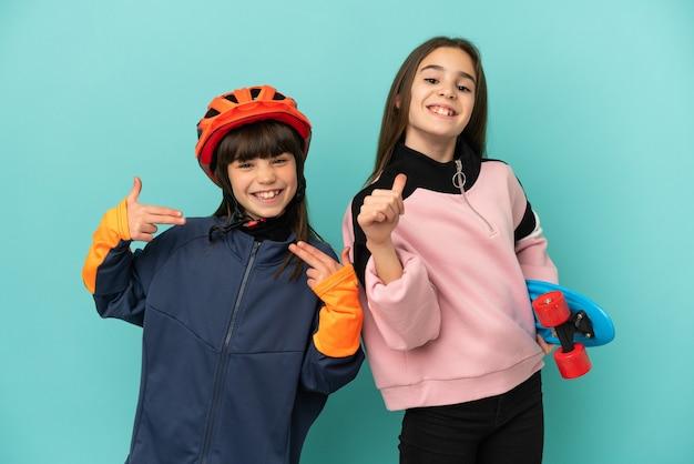 Kleine zusjes beoefenen fietsen en skater geïsoleerd op blauwe achtergrond trots en zelfvoldaan in liefde jezelf concept