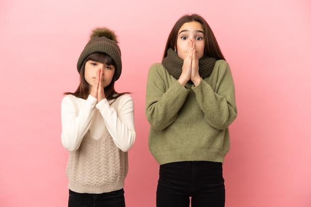 Kleine zusjes die een winterkleren dragen die op een roze achtergrond zijn geïsoleerd, houden de palm bij elkaar. persoon vraagt om iets