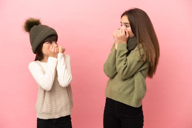 Kleine zusjes die een winterkleren dragen die op roze achtergrond worden geïsoleerd, zijn een beetje nerveus en bang om hun handen op de mond te leggen