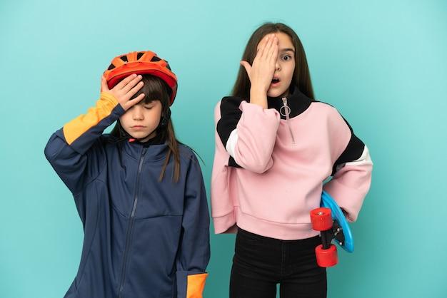 Kleine zusjes die fietsen beoefenen en skater geïsoleerd met verbazing en geschokte gezichtsuitdrukking