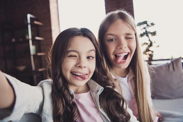Kleine zusjes die samen op de bank poseren