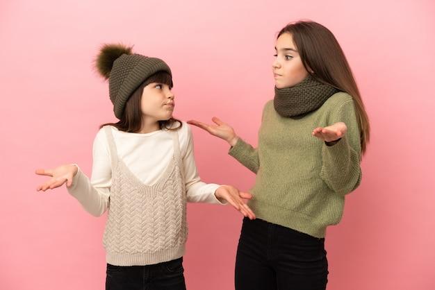 Kleine zusjes die winterkleren dragen geïsoleerd op een roze achtergrond die een onbelangrijk gebaar maken terwijl ze de schouders optillen