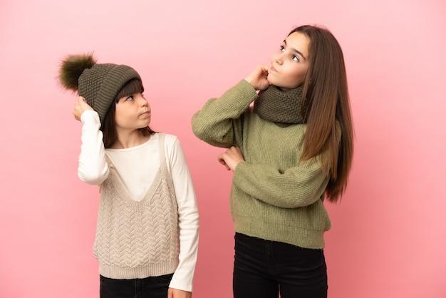 Kleine zusjes dragen een winterkleren geïsoleerd op een roze achtergrond en denken een idee terwijl ze aan het hoofd krabben