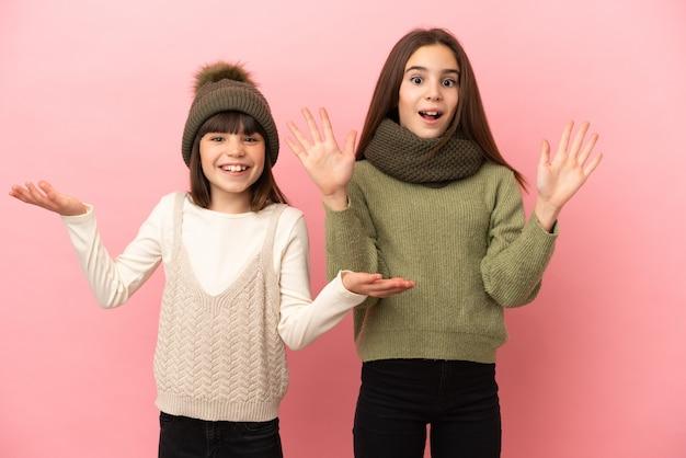 Kleine zusjes dragen een winterkleren geïsoleerd op een roze achtergrond met verrassing en geschokte gezichtsuitdrukking