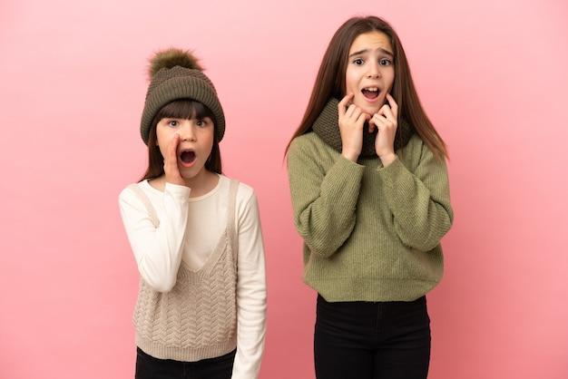 Kleine zusjes dragen winterkleren geïsoleerd op roze achtergrond verrast en geschokt terwijl ze naar rechts kijken