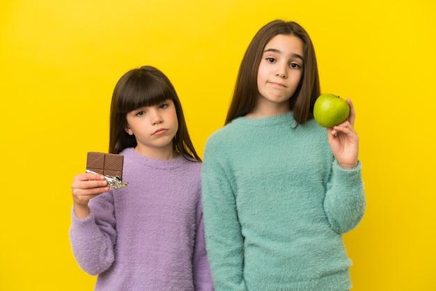 Kleine zusjes geïsoleerd op een gele achtergrond met een chocoladetablet in de ene hand en een appel in de andere