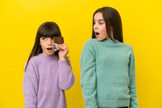 Kleine zusjes geïsoleerd op gele achtergrond die een chocoladetablet nemen en verrast