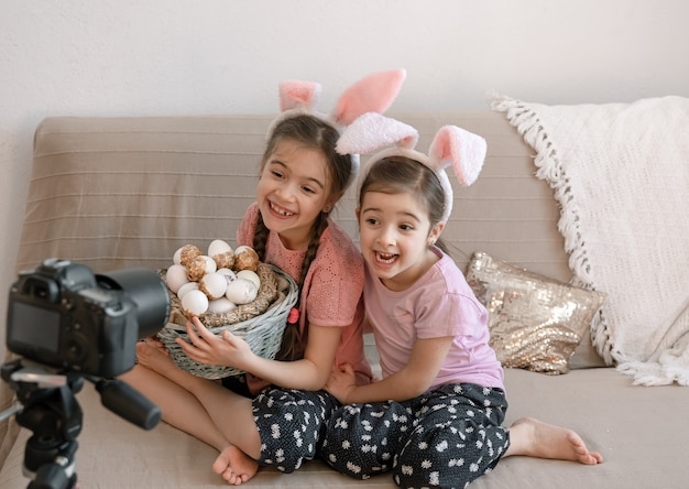 Kleine zusjes in konijnenoren poseren voor de camera met een mandje met vakantie-eieren