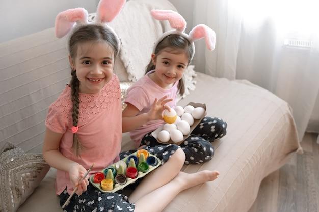 Kleine zusjes in konijnenoren schilderen paaseieren op de bank thuis