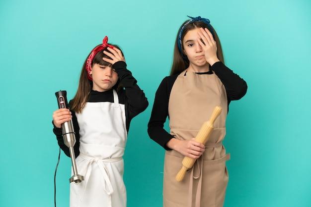 Kleine zusjes koken thuis geïsoleerd met verbazing en geschokte gezichtsuitdrukking