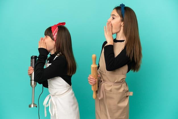 Kleine zusjes koken thuis geïsoleerd op blauwe achtergrond schreeuwend met mond wijd open naar de laterale