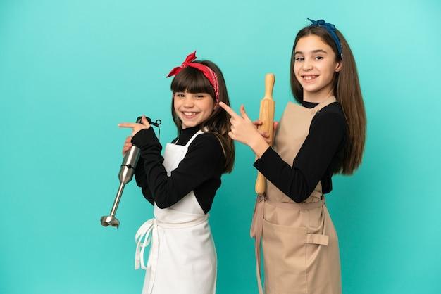 Kleine zusjes koken thuis geïsoleerd op een blauwe achtergrond wijzende vinger naar de zijkant in zijpositie