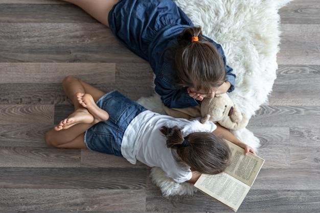 Kleine zusjes lezen een boek met een teddybeer die op de vloer ligt in het bovenaanzicht van de kamer.