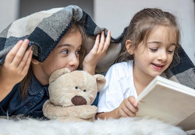 Kleine zusjes lezen een boek met een teddybeer op de vloer in de kamer.