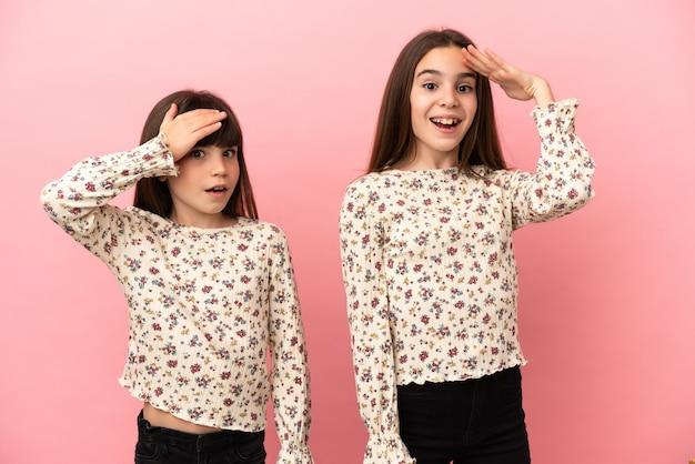 Kleine zusjes meisjes geïsoleerd op roze achtergrond hebben net iets gerealiseerd en hebben de oplossing bedacht