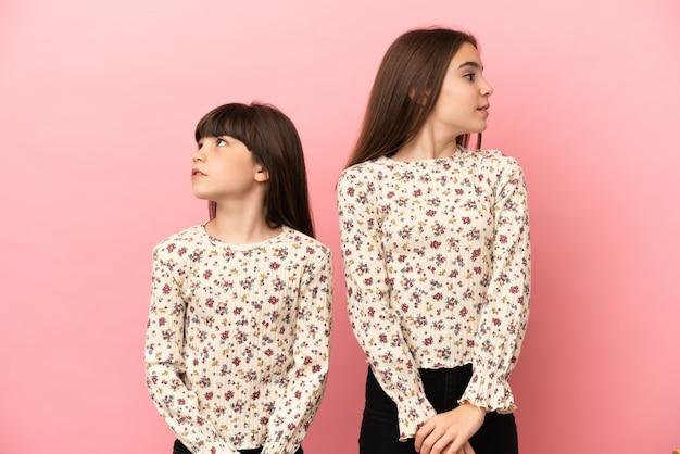 Kleine zusjes meisjes geïsoleerd op roze achtergrond nerveus en bang