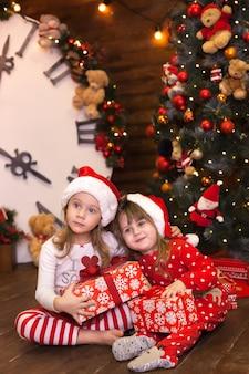 Kleine zusjes meisjes in rode pyjama's versieren kerstboom en open geschenken in de woonkamer