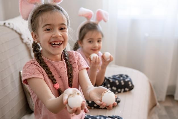 Kleine zusjes met konijnenoren en paaseieren poseren voor de camera op de bank thuis