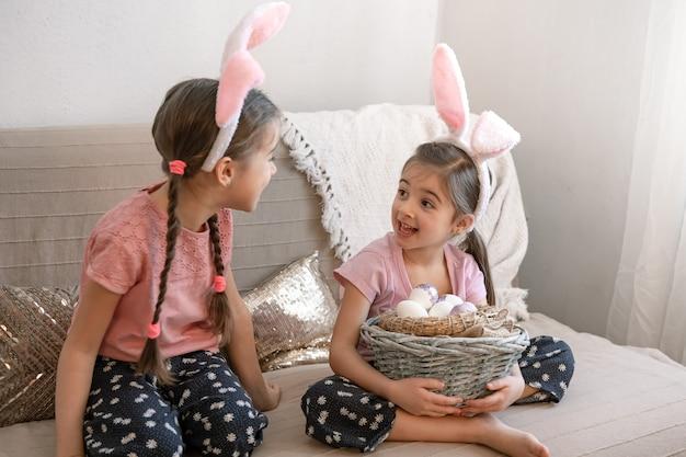 Kleine zusjes met konijnenoren, met paaseieren thuis op de bank