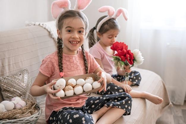 Kleine zusjes met konijnenoren poseren met paaseieren en bloemen ter decoratie