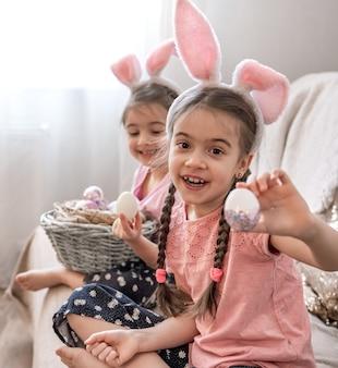 Kleine zusjes met konijnenoren poseren met paaseieren