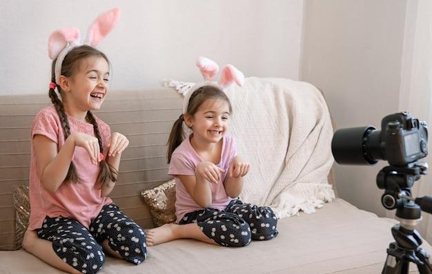 Kleine zusjes met konijnenoren poseren voor de camera met konijnen