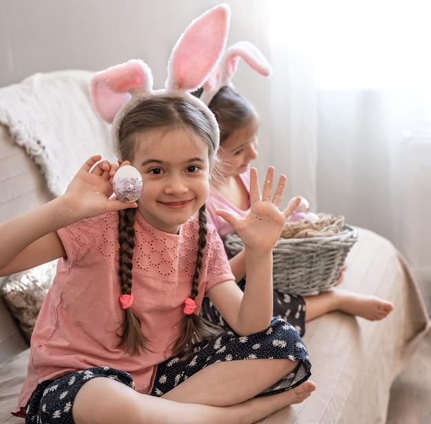 Kleine zusjes met konijnenoren poseren voor de camera met paaseieren