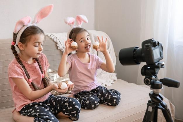 Kleine zusjes met konijnenoren poseren voor de camera op de bank thuis
