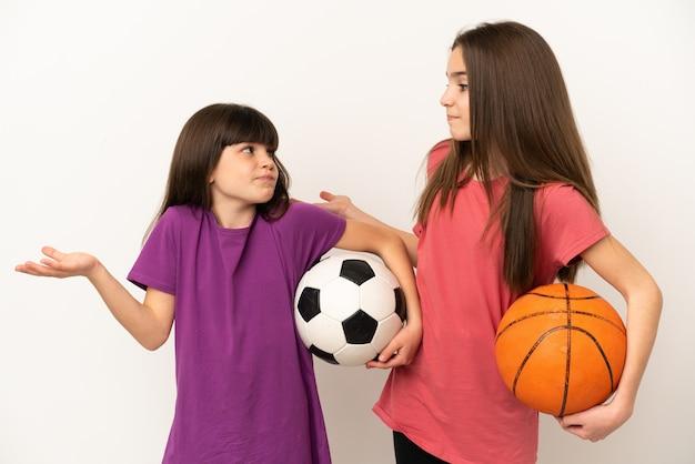 Kleine zusjes voetballen en basketballen geïsoleerd op een witte achtergrond die een onbelangrijk gebaar maken terwijl ze de schouders optillen