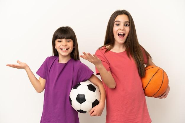 Kleine zusjes voetballen en basketballen geïsoleerd op een witte achtergrond met verrassing en geschokte gezichtsuitdrukking