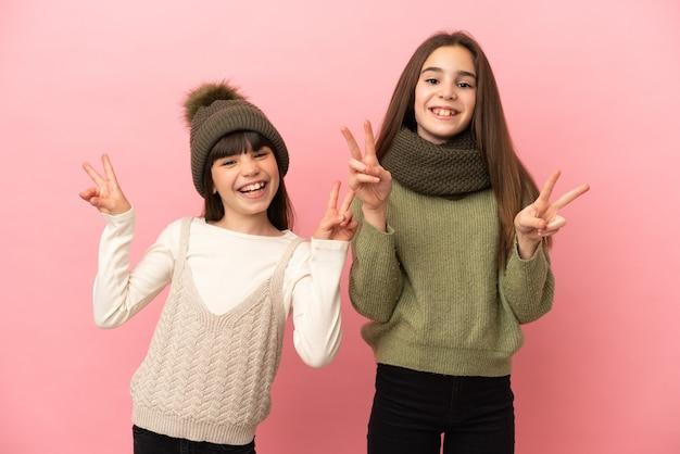 Kleine zusters die een winterkleren dragen die op roze achtergrond worden geïsoleerd en glimlachen en overwinningsteken met beide handen tonen