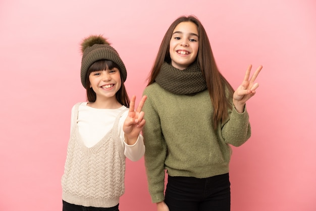 Kleine zusters die winterkleren dragen die op roze achtergrond worden geïsoleerd glimlachen en tonen overwinningsteken