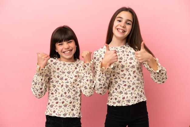 Kleine zusters meisjes geïsoleerd geven een duim omhoog gebaar met beide handen en glimlachen