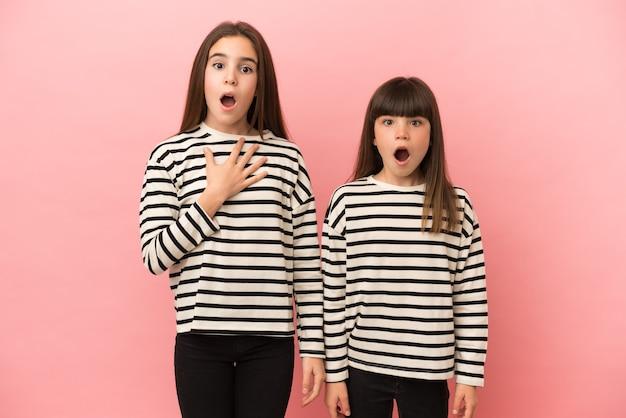Kleine zusters meisjes geïsoleerd met verrassing en geschokte gezichtsuitdrukking