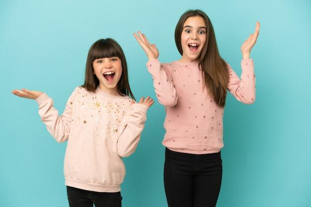 Kleine zusters meisjes geïsoleerd op blauwe achtergrond met verbazing en geschokt gelaatsuitdrukking