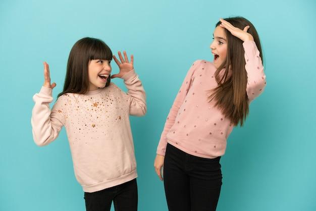 Kleine zusters meisjes geïsoleerd op blauwe achtergrond met verrassing en geschokte gezichtsuitdrukking