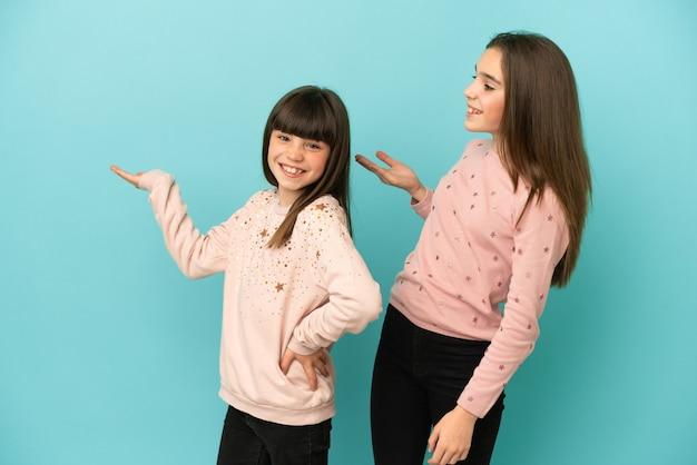 Kleine zusters meisjes geïsoleerd op blauwe achtergrond terug te wijzen en een product te presenteren