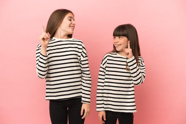Kleine zusters meisjes geïsoleerd op roze achtergrond met de bedoeling de oplossing te realiseren terwijl ze een vinger optillen