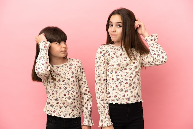 Kleine zusters meisjes geïsoleerd op roze achtergrond met twijfels tijdens het hoofd krabben