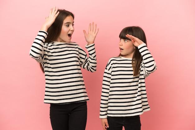 Kleine zusters meisjes geïsoleerd op roze achtergrond met verbazing en geschokt gelaatsuitdrukking