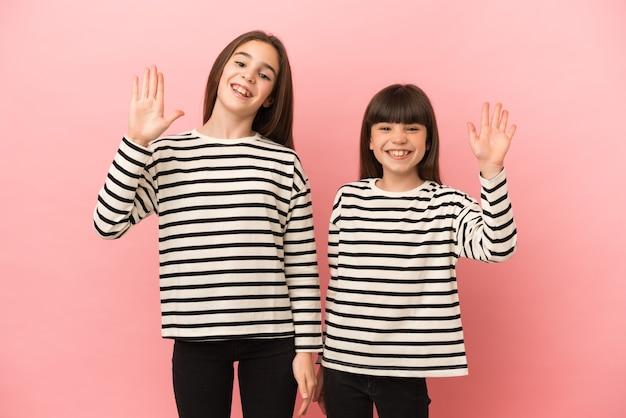 Kleine zusters meisjes geïsoleerd saluerend met de hand met gelukkige uitdrukking