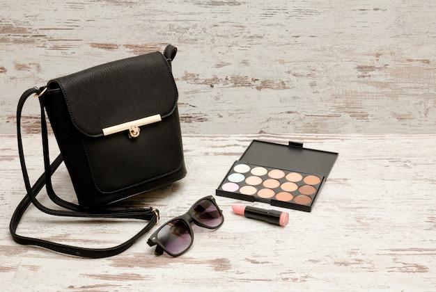 Kleine zwarte dames handtas, zonnebril, lippenstift en oogschaduw op houten achtergrond