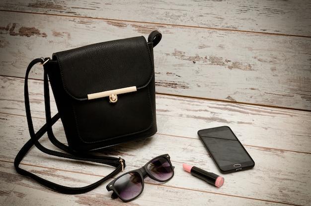 Kleine zwarte dames handtas, zonnebril, telefoon en lippenstift op houten achtergrond. mode concept