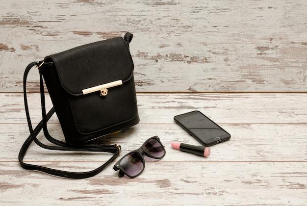 Kleine zwarte dames handtas, zonnebril, telefoon en lippenstift op houten. mode