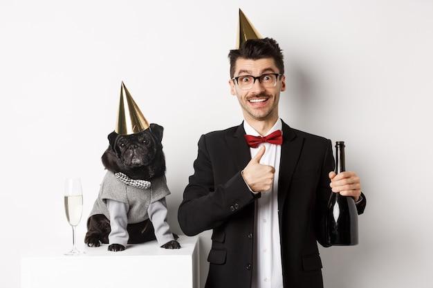 Kleine zwarte hond met feestmuts en staande in de buurt van gelukkige man die vakantie viert, eigenaar die duim omhoog laat zien en champagnefles vasthoudt, witte achtergrond