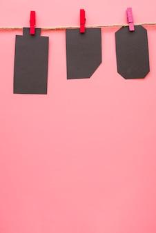 Kleine zwarte papieren labels hangen aan draad