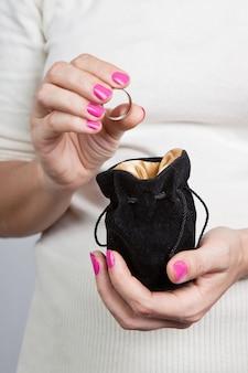 Kleine zwarte tas voor sieraden in de handen van vrouwen