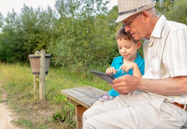Kleinkind leert zijn grootvader om een elektronische tablet te gebruiken op een bankje in het park. focus op opa. generatie waarden concept.